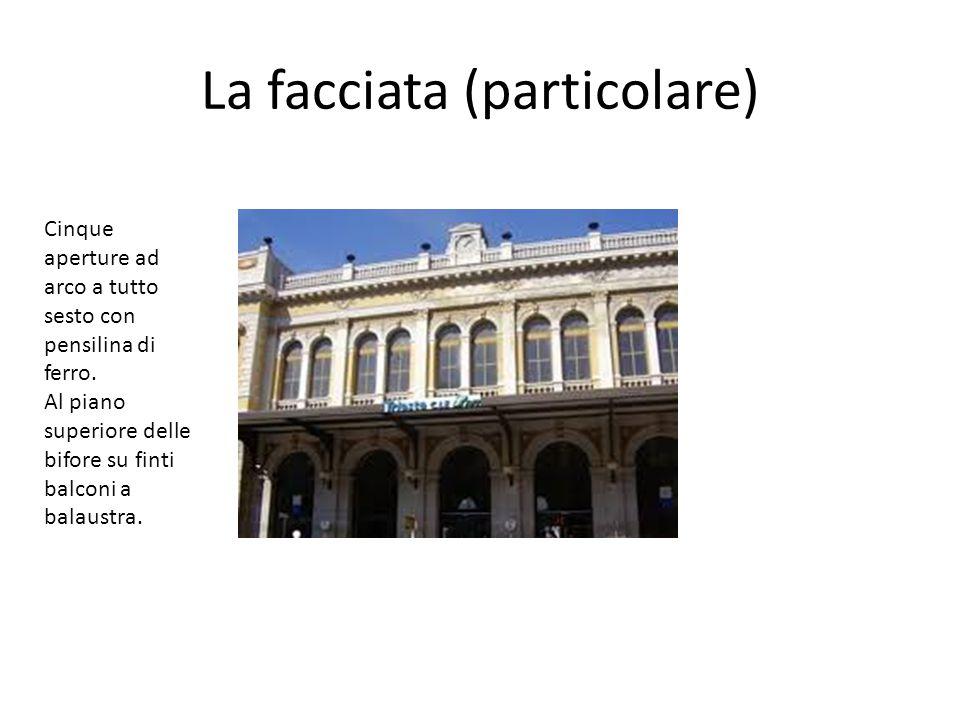 La facciata (particolare) Cinque aperture ad arco a tutto sesto con pensilina di ferro. Al piano superiore delle bifore su finti balconi a balaustra.