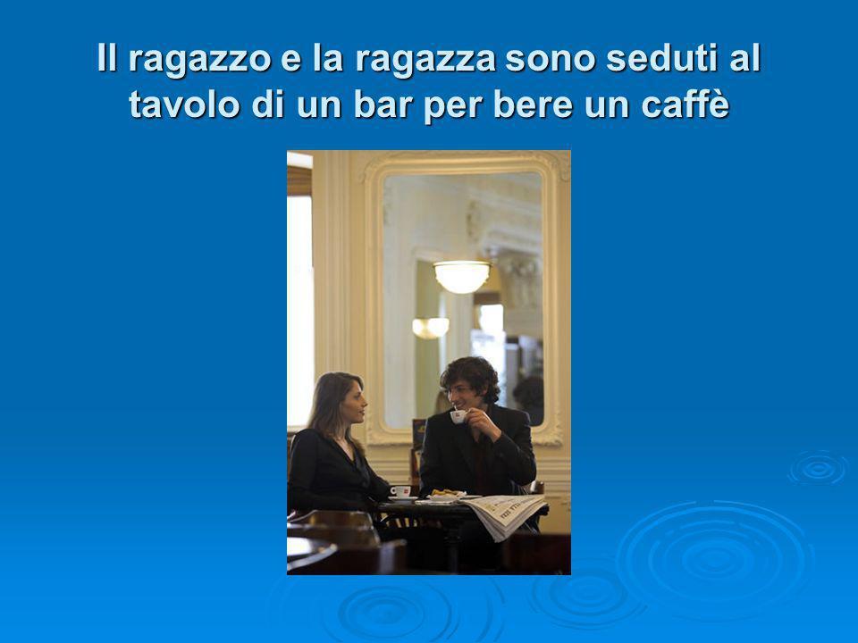 Il ragazzo e la ragazza sono seduti al tavolo di un bar per bere un caffè