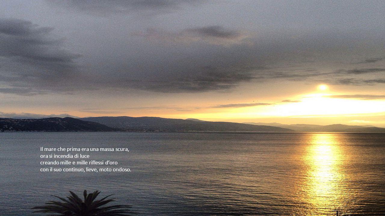 Il mare che prima era una massa scura, ora si incendia di luce creando mille e mille riflessi d'oro con il suo continuo, lieve, moto ondoso.